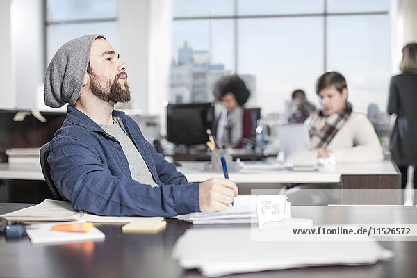 Mann mit Bleistift am Schreibtisch im Büro denken