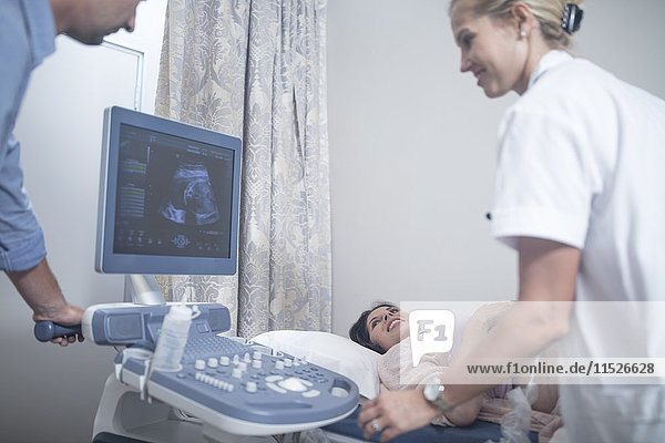 Arzt im Krankenhaus beim Sonogramm mit schwangerer Frau