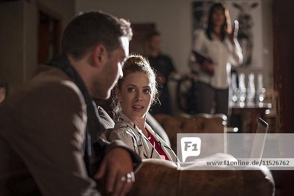 Frau mit Laptop auf dem Sofa im Gespräch mit dem Mann