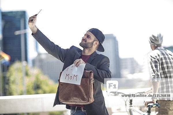 Junger Geschäftsmann schickt Selfie zu seiner Mutter.