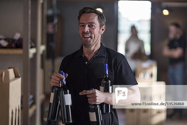 Porträt eines lächelnden Mannes mit Weinflaschen im Geschäft
