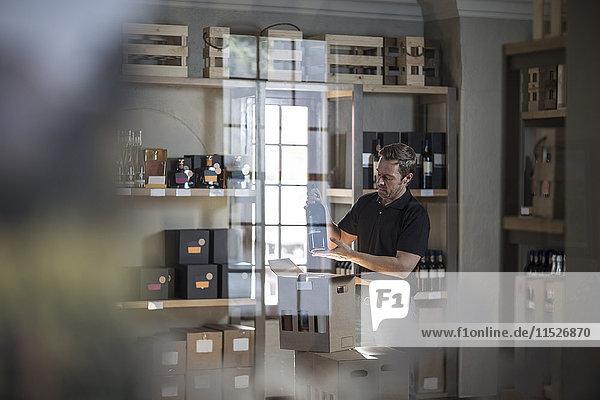 Mann mit Weinflasche im Laden