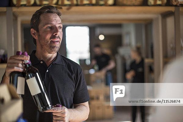 Mann präsentiert Wein im Geschäft