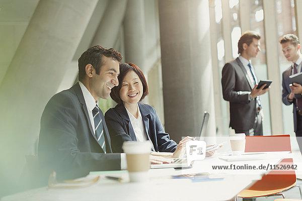 Geschäftsmann und Geschäftsfrau bei der Arbeit am Laptop im Konferenzraum