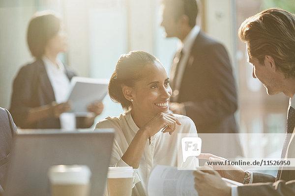 Lächelnde Geschäftsleute diskutieren Papierkram im Meeting