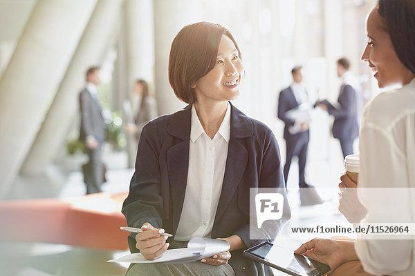 Lächelnde Geschäftsfrauen treffen sich  um den Papierkram in der Bürolobby zu besprechen.