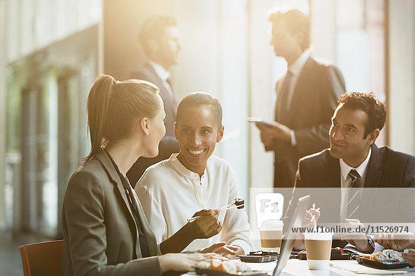 Geschäftsleute beim Mittagessen mit Essstäbchen im Konferenzzimmer