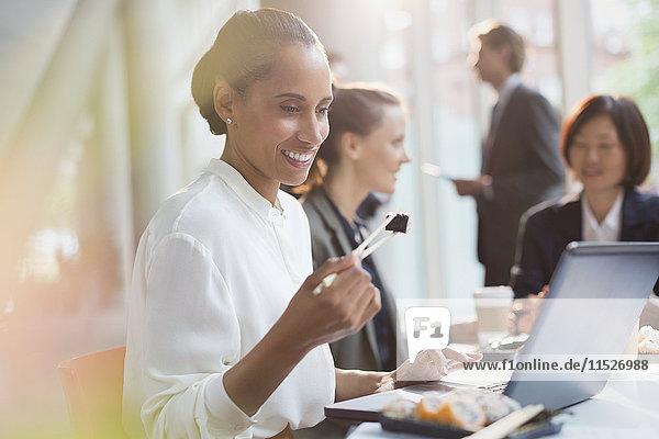 Lächelnde Geschäftsfrau beim Sushi-Lunch mit Essstäbchen am Laptop im Konferenzraum Meeting