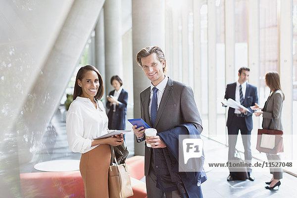 Portrait lächelnder Geschäftsmann und Geschäftsfrau in sonniger Bürolobby