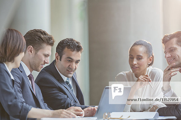 Business people using laptop in conference room meeting