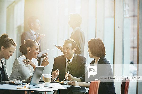 Lächelnde Geschäftsleute beim Sushi-Lunch mit Essstäbchen im Konferenzraum Meeting