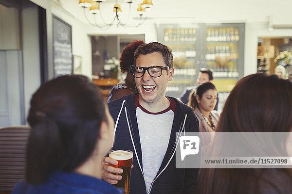 Mann lacht und trinkt Bier mit Freunden an der Bar