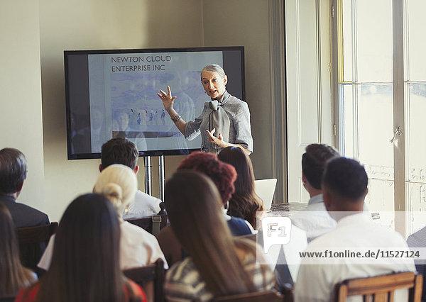 Geschäftsfrau leitet Konferenzpräsentation am Fernsehbildschirm