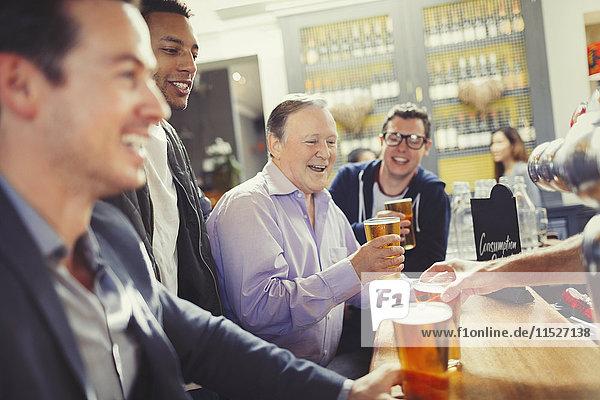Smiling men friends drinking beer at bar