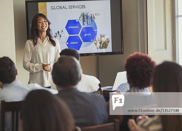 Lächelnde Geschäftsfrau bei der Präsentation einer Geschäftskonferenz am Bildschirm