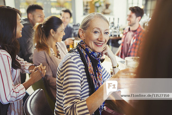 Lächelnde Seniorin trinkt und redet mit einer Freundin in der Bar.