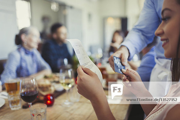 Frau überprüft die Rechnung und bezahlt den Kellner mit Kreditkarte am Restauranttisch.