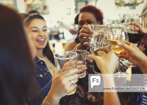 Enthusiastic women celebrating  toasting beer and wine glasses at bar