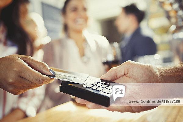 Frau mit Kreditkarte zahlender Barkeeperin mit kontaktloser Bezahlung an der Bar