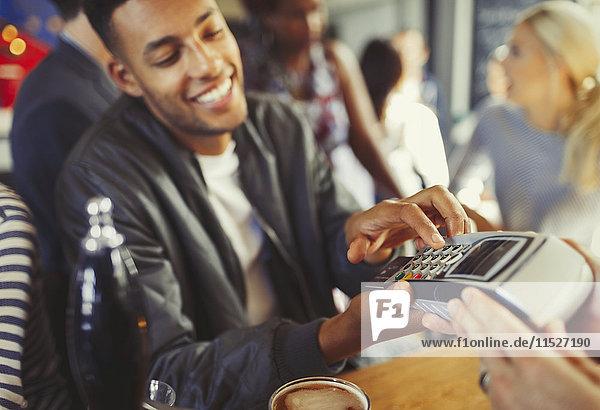 Smiling man paying bartender using credit card reader at bar