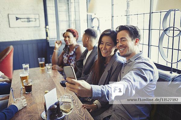 Lächelndes Paar nimmt Selfie mit Fotohandy am Tisch in der Bar mit.
