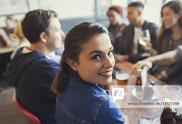 Portrait lächelnde Frau beim Biertrinken mit Freunden am Tisch in der Bar