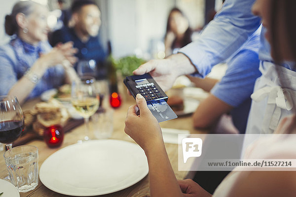 Frau mit kreditkartenzahlendem Kellner  mit Kreditkartenleser am Restauranttisch