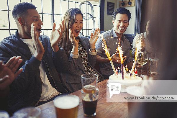 Freunde feiern Geburtstag mit Feuerwerkstorte am Tisch in der Bar