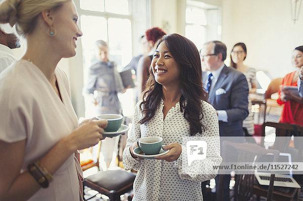 Lächelnde Geschäftsfrauen beim Kaffeetrinken und Networking auf der Business-Konferenz