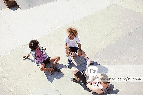 Draufsicht männliche Freunde im sonnigen Skatepark