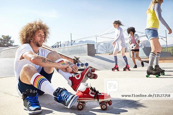 Mann auf Rollschuhen im sonnigen Skatepark