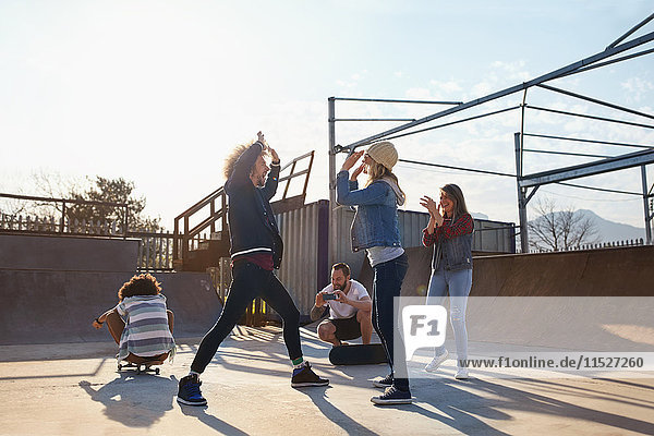 Freunde High-Fiving im sonnigen Skatepark
