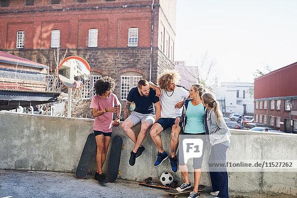 Freunde mit Skateboards an der urbanen Sommerwand