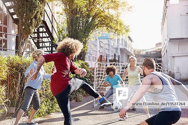 Freunde spielen Fußball in der sonnigen Sommerstraße