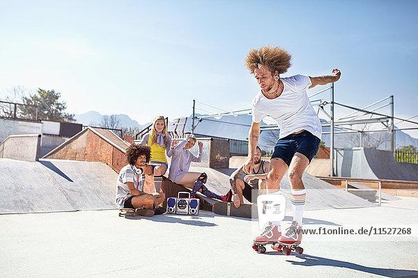 Freunde beim Rollschuhlaufen im sonnigen Skatepark