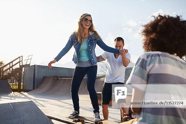 Freund hilft Freundin auf dem Skateboard im sonnigen Skatepark
