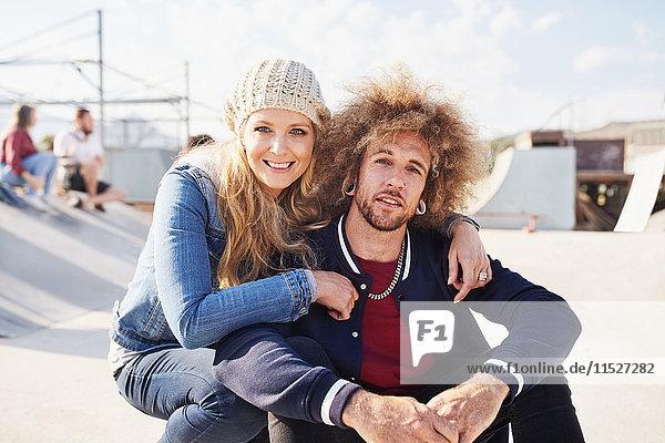 Portrait lächelndes Paar im sonnigen Skatepark