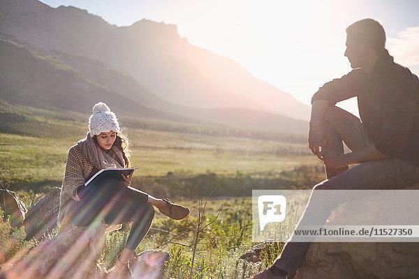 Junges Paar beim Wandern  Ausruhen und Schreiben im sonnigen  abgelegenen Feld