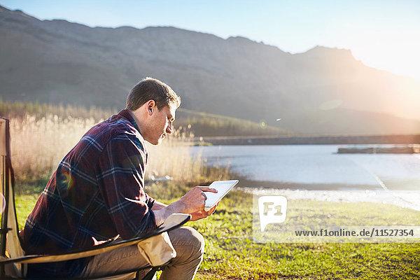 Junger Mann mit digitalem Tablett am sonnigen Seeufer