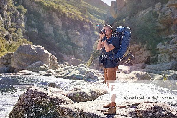 Junger Mann mit Rucksackwanderung  Fotografieren mit Kamera auf sonnigen Felsen