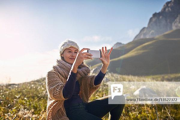 Junge Frau mit Fotohandy im sonnigen  abgelegenen Tal