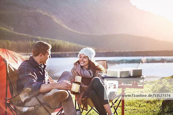 Lächelndes junges Paar trinkt Kaffee auf dem sonnigen Campingplatz am See.