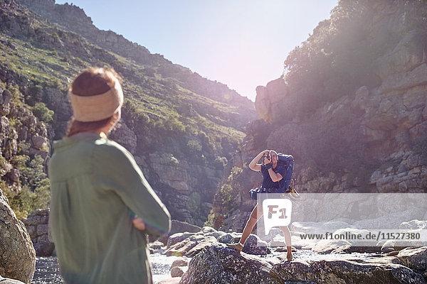 Junge Frau beobachtet Freund beim Wandern  fotografiert zerklüftete Klippen