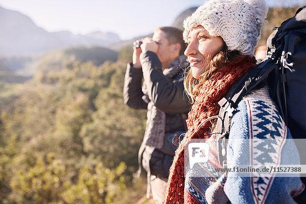 Junges Paar beim Wandern  Blick auf die Sonne mit dem Fernglas