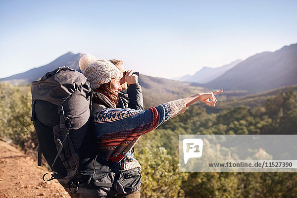 Young couple hiking  looking at sunny view with binoculars
