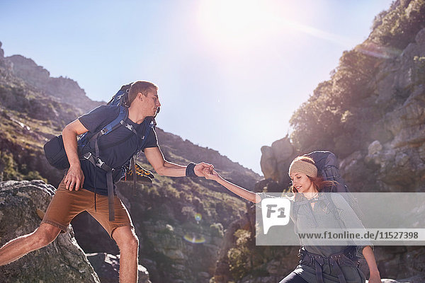 Junger Mann hilft Freundin beim Wandern unter sonnigen  zerklüfteten Klippen