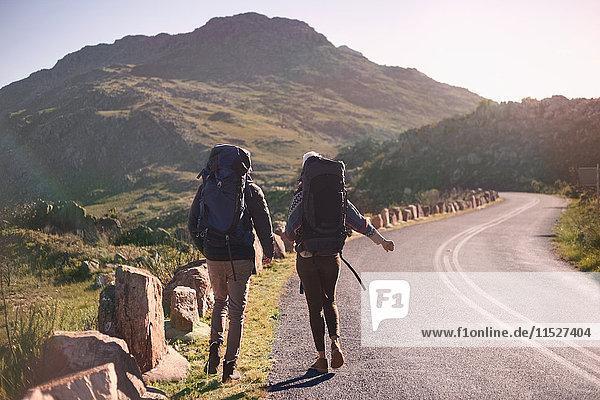 Junges Paar mit Rucksäcken auf sonnigen  abgelegenen Straßenrändern