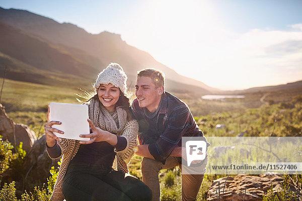 Junges Paar nimmt Selfie mit digitaler Tablettkamera im sonnigen Tal auf