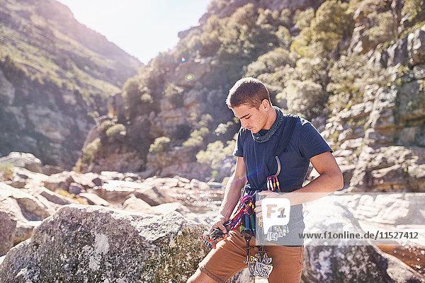 Junger Mann beim Vorbereiten von Kletterkarabinern und Ausrüstung zwischen sonnigen Felsen