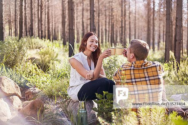 Junges Paar beim Zelten  Kaffeetassentoasten in sonnigen Wäldern